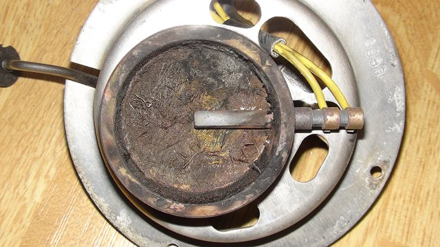 De sterk vervuilde brander met gloeistift nadat grotere harde aangekoekte brokken al waren verwijderd